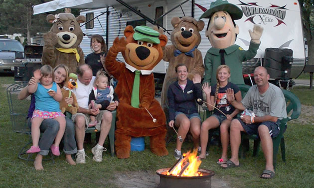 Jellystone guests and costumed characters around a campfire.