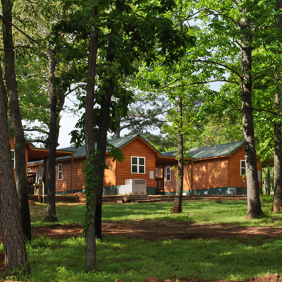 Picture of wooden cabins seen through a grove of trees.