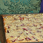 Hands hold a baking sheet containing a fruit crumble.