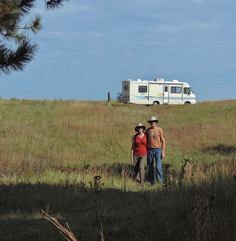 A photo of Kevin and Ruth Read in the forground, and Sherman their motorhome on a grassy hill in the background.
