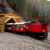 The Kimberley Underground Mining Railway little red train exits a log tunnel structure.