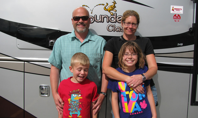 Couple with two young children and a large RV behind them