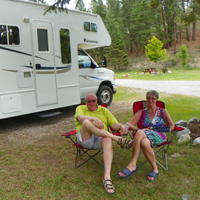 Peter and Margreet relax in their Canadian camping chairs in a quiet RV lot.