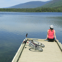 A woman sits on a dock looking over a lake with a bike beside her.