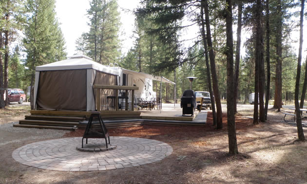 RV with an attached gazebo-style room and awning, wooden deck and adjacent fireplace