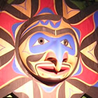 A large decorative carved native mask resembles a sun with a central face and arms that look like birds. It is painted in reds, purples and browns.