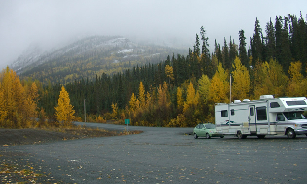 Rae's RV, hauling a green hatchback, is parked to the right against yellow autumn trees and a misty mountain background.