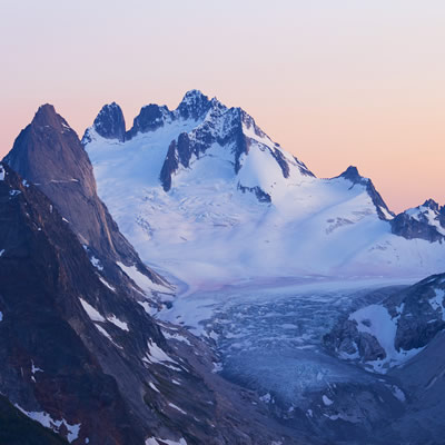 Mountain range with snow, pink sky background.