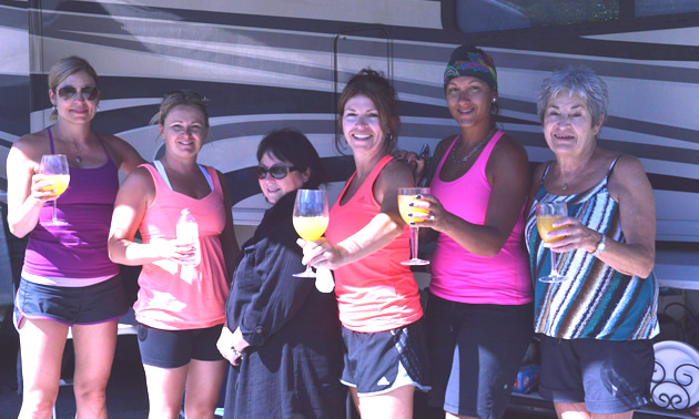 A row of smiling women wearing casual summer clothing and holding out stemmed glasses of orange liquid