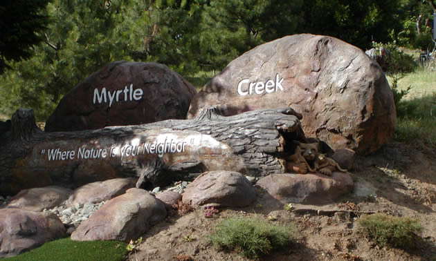 Natural rounded boulders and rocks bear the words Myrtle Creek; a log lying in front of the rocks bears the words