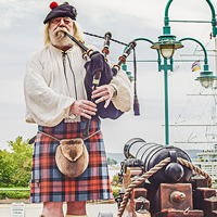 A bagpipe player in traditional dress stands between two cannons.