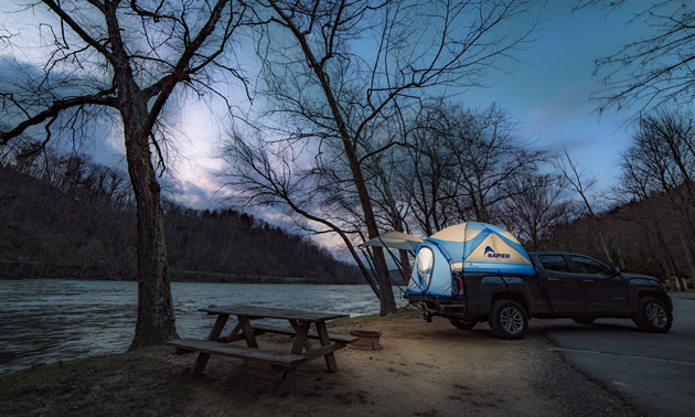 A lantern lit Truck Tent by a river at night.