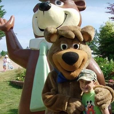 Child posing with a Yogi Bear mascot.