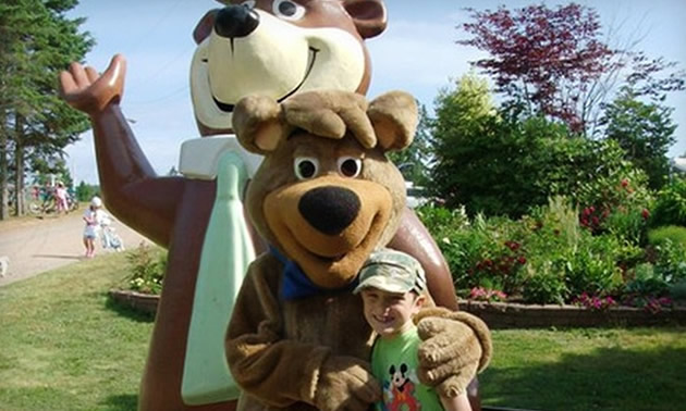 Child posing with a Yogi Bear mascot.