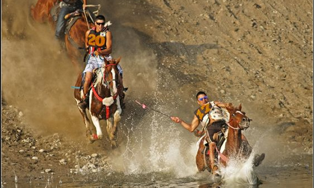 Picture of horses and riders coming down a steep bank beside a river.