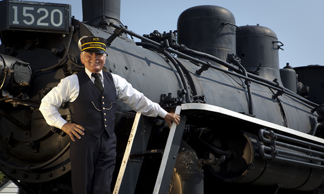 A train conductor stands posed on the front of an antique engine.
