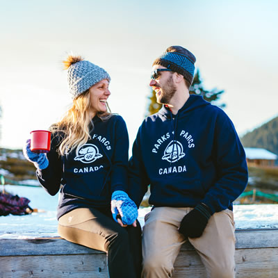 Man and woman sitting together wearing navy blue hoodies with Parks Canada logo. Woman is holding red mug.