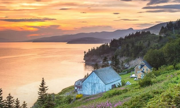View of quaint lakeside cabin, with sunset.