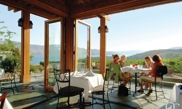 Four women sit at a dining table on a patio overlooking vineyards, lake, low mountains and sky