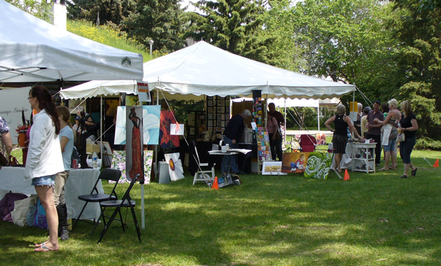 White tents full of busy people and works of art are scattered across sun-dappled green grass.