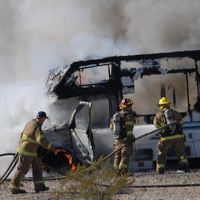 Picture of three firemen putting out RV fire