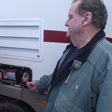Runners RV service technician Lloyd Panchuk checks voltage on a furnace as Service Manager Tom Gilgan look on.