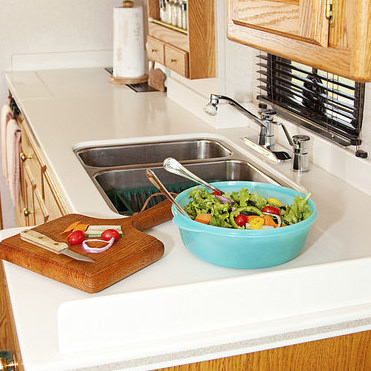 A photo of an RV kitchen with a salad and cutting board in the countertop.