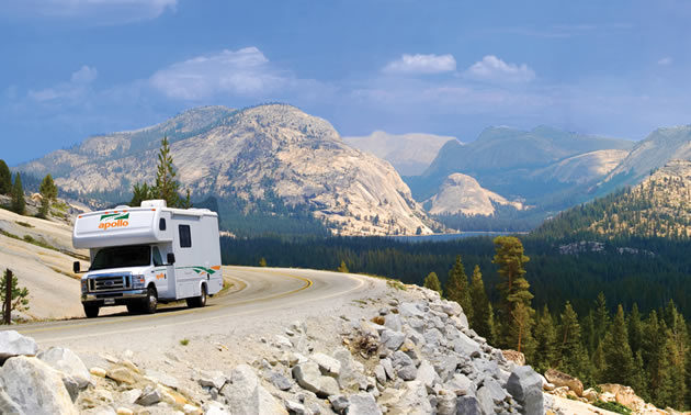 Picture of camper travelling on highway with mountain scene in background.