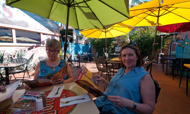 Two women sitting at patio table, holding and reading magazines.