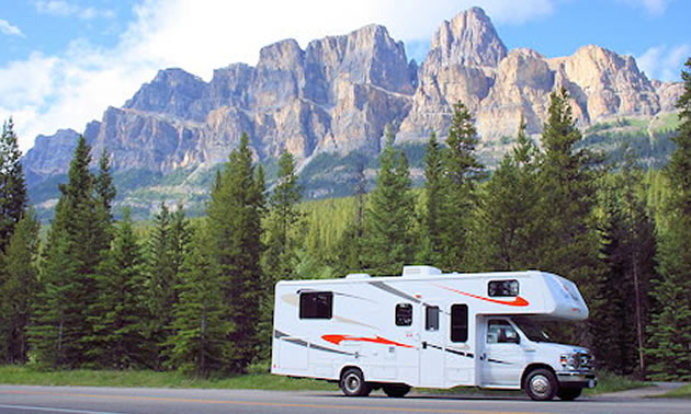 Picture of RV with towering mountains and pine tree in the background.