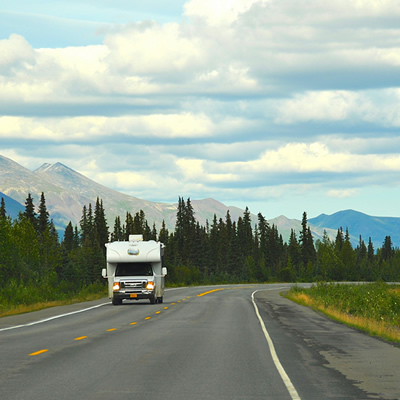 A picture of an RV travelling down a road.