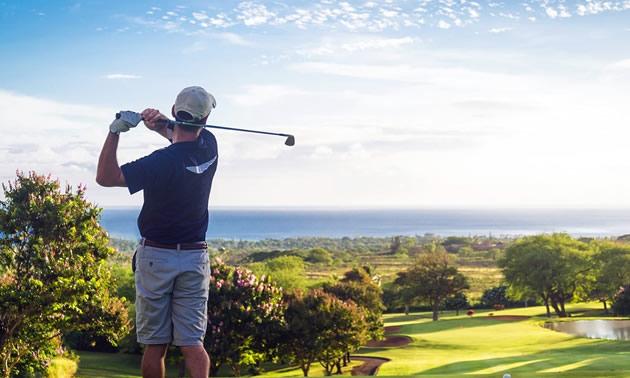 Man golfing with ocean vista in background.
