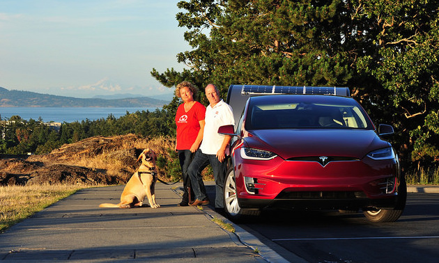 Rolf Oetter and Silke Sommerfeld standing outside of their Telsa Model S.