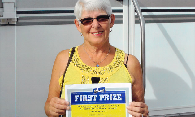 Donna Leslie with her winner's certificate and RV.