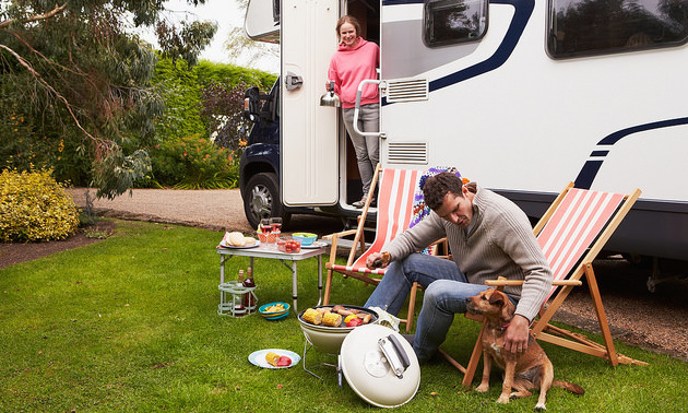 Couple In an RV enjoying barbecue on camping holiday.  The man is sitting in a lawn chair leaning over and petting his dog.