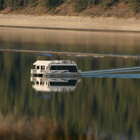 Houseboat on calm water that mirrors the shore and trees