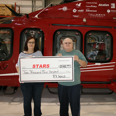 Duane and Lynda Pilson proudly present STARS with a cheque for $2,400 gathered at the 11th Annual RV West Rally held in Stettler.