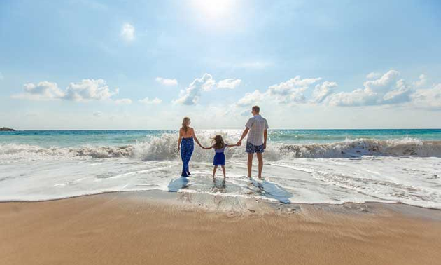 Family enjoying day at beach, wading into incoming tide.