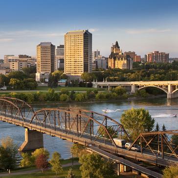 Saskatoon's skyline is illuminated between river and blue sky. A bridge visually leads you into the city.
