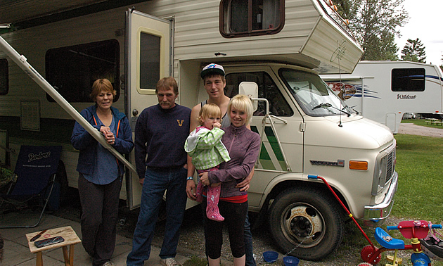 Grandparents, young couple and toddler stand beside their RV.