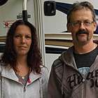 Couple stands with their German shepherd beside their motorhome.