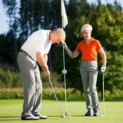 A man and a woman setting up a golf shot.