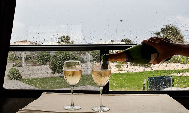 Bubbles in two wine glasses on a table in an RV mimic the rain on the window at Gulf Waters in Texas.