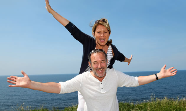 A couple posing in front of ocean scene.