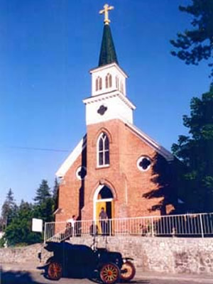 Rathdrum's St. Stanislaus Church is made of red bricks with a white steeple.
