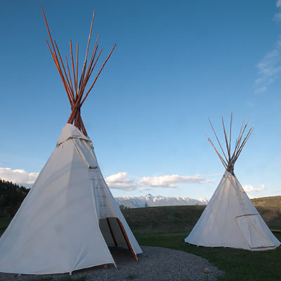 Two teepees made of white canvas, set up in a camp at St. Eugene RV Park, with a view of Rocky Mountains in the distance.