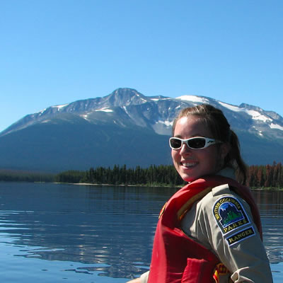 BC Parks student ranger in canoe on lake, looking over her shoulder at camera.