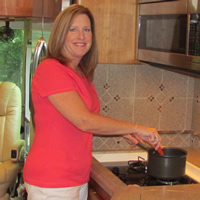 Sylvia stands in her RV kitchen smiling at the camera while cooking in a saucepan.