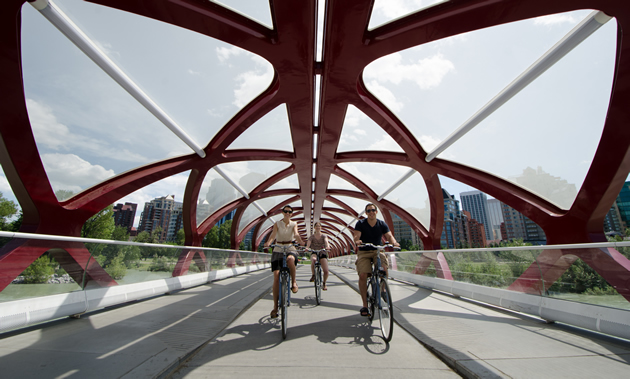 Three bikers smile as they pedal beneath the futuristic red