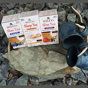 Three boxes of Hyleys tea displayed by two blue pottery mugs hanging on an antler on rocks